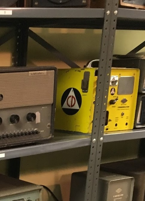 Rack of old radio equipment showing a yellow Gonset Communicator